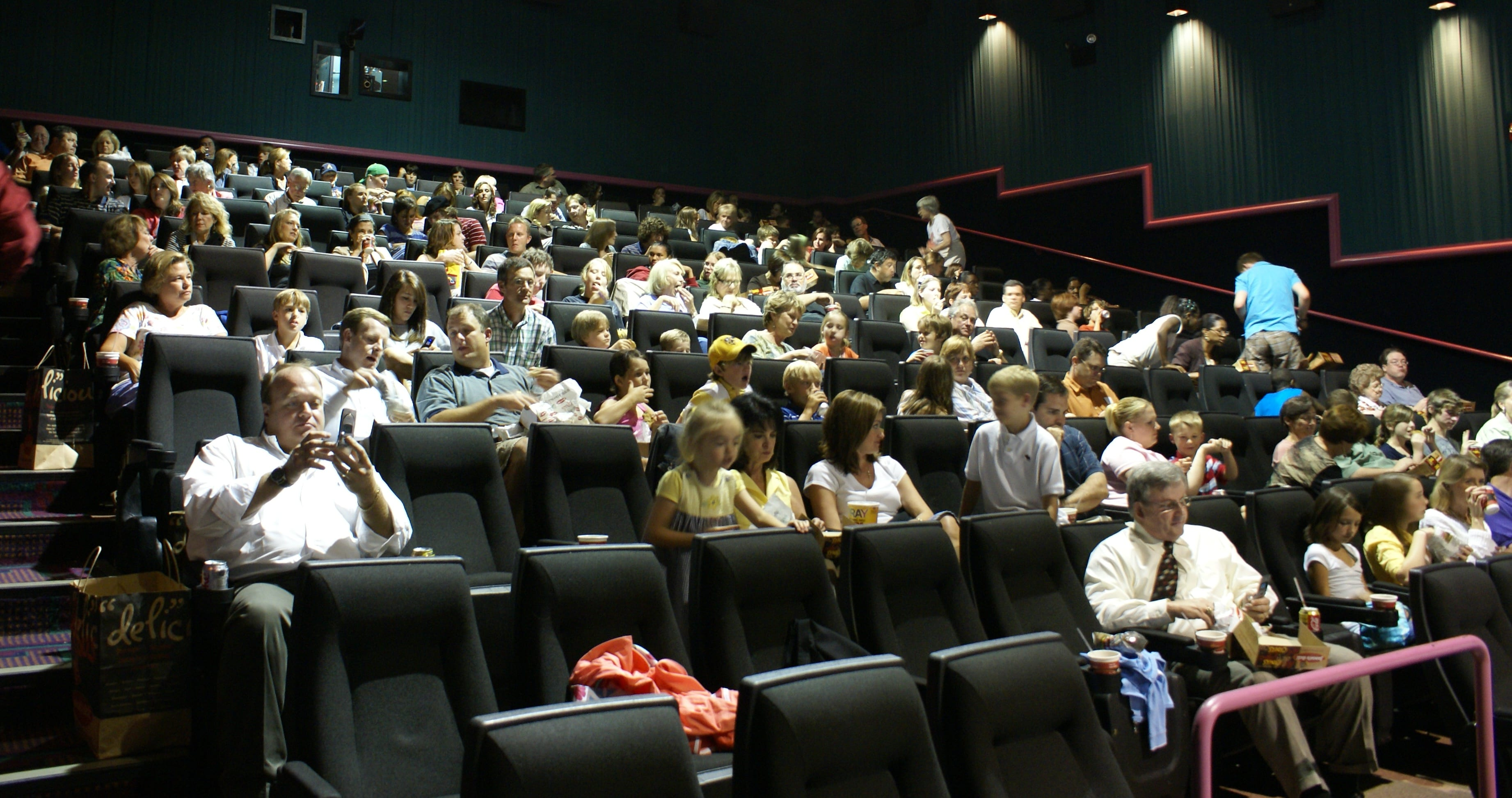 impatient theatre goers wait for the film to start
